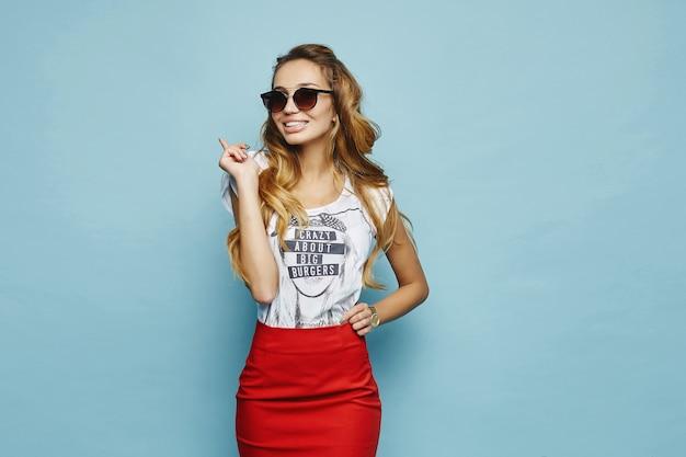 Веселая белокурая молодая женщина в белой футболке, в красной юбке и очках улыбается и позирует Premium Фотографии
