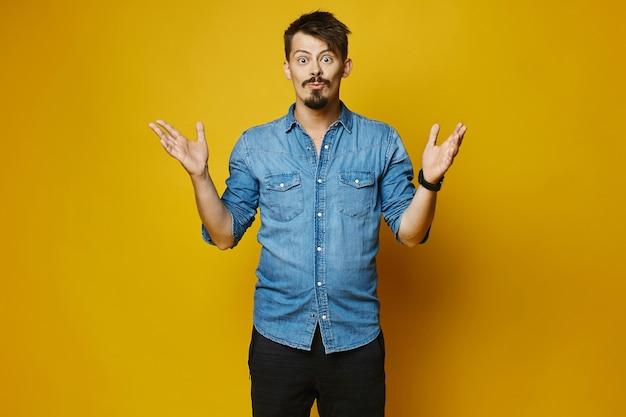 Удивленный молодой человек, стильный хипстер с бородой и усами в модной джинсовой рубашке Premium Фотографии