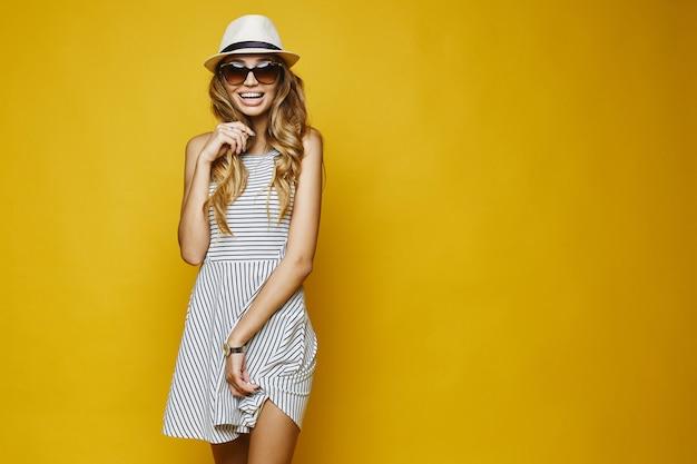 白いドレス、帽子、サングラスで表現力豊かなブロンドの女の子 Premium写真