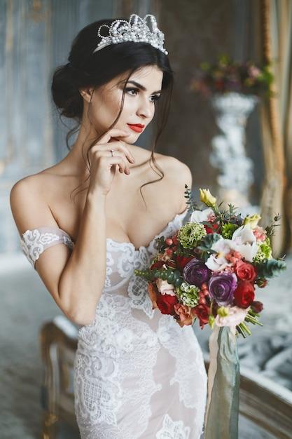 Молодая невеста в кружевном платье позирует с букетом невесты Premium Фотографии