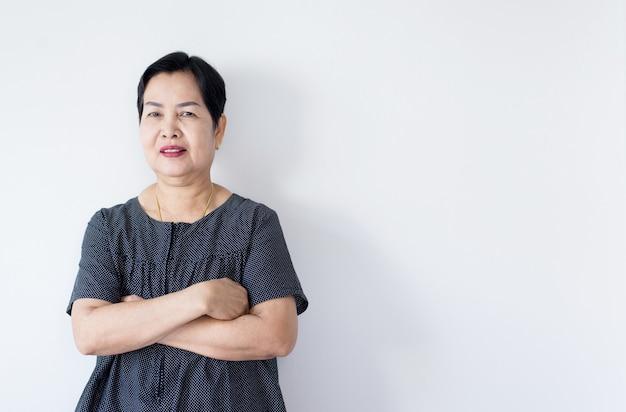 Портрет красивой пожилой азиатской женщины, стоящей крест руками и смотрящей камеру в помещении, счастливые и улыбающиеся лица, скопируйте пространство для текста на белом фоне Premium Фотографии