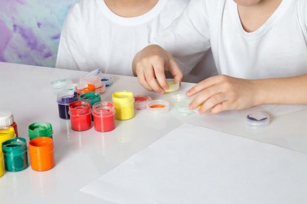 色とりどりのカラフルな絵の具で遊ぶ男の子たち 無料写真