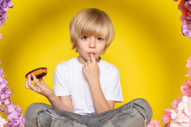 Вид спереди белокурый мальчик в белой футболке ест пончики шоколад, сидя на цветок сделал стойку на желтом пространстве Бесплатные Фотографии