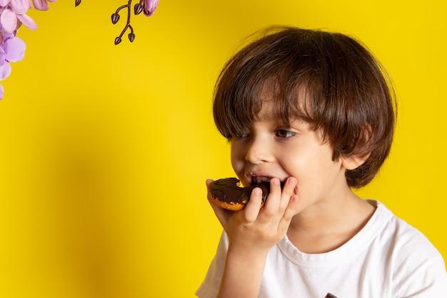 Мальчик вид спереди ест пончики с шоколадом на желтом пространстве Бесплатные Фотографии