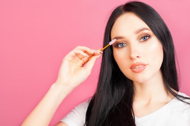 女性はまつげをマスカラブラシで、顔をクローズアップで、ピンクの壁にコピースペースでとかします。エクステンションやマスカラとメイクのコンセプトです。 Premium写真