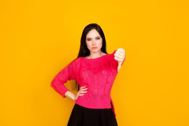 親指を下にして、明るい白い壁に女性を示しています。不承認と低品質、評価が低く、結果が悪いという概念。 Premium写真