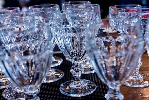 レストランのバーラックの上の棚のワインとマティーニのグラス。空のきれいなグラスのバー。 Premium写真