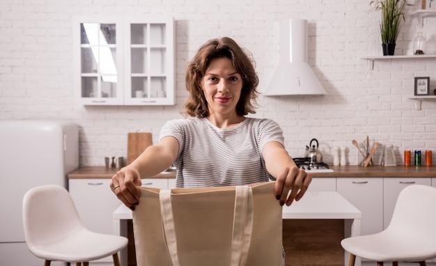 布の袋を保持している若い女性。キッチンで。私はプラスチックではありません。ビニール袋使用量削減キャンペーン。廃棄物ゼロ Premium写真