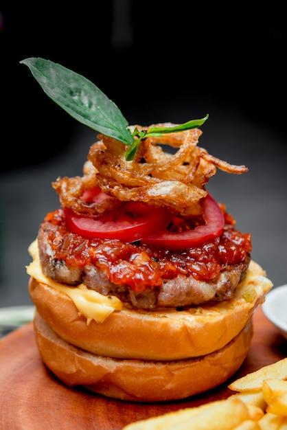 食欲をそそるハンバーガーとチーズと野菜。バーベキュー。 Premium写真