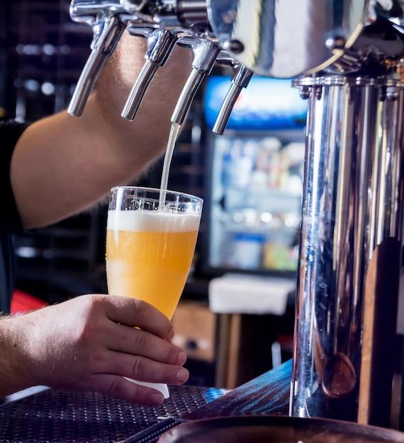 Бармен разливает разливное пиво по бокалам в баре. ресторан. Premium Фотографии