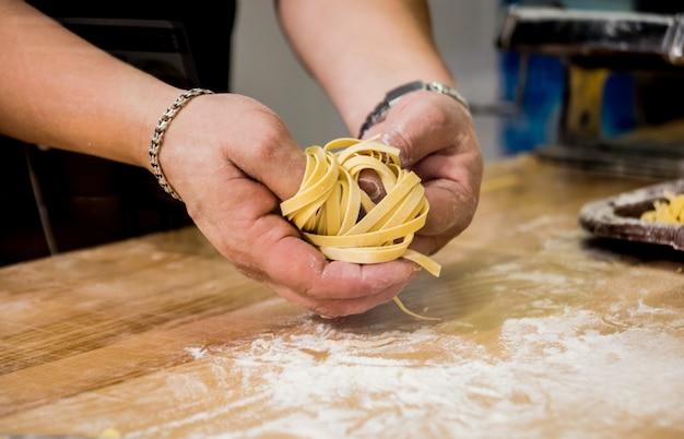 Шеф-повар раскатывает тесто с помощью макаронной машины. машина для производства макаронных изделий. Premium Фотографии