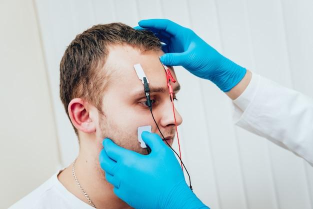Нервы пациента проверяются с помощью электромиографии. Premium Фотографии
