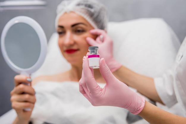 Врач косметолог проводит процедуру инъекций лица. Premium Фотографии