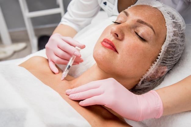 Врач косметолог проводит процедуру инъекций декольте. молодая женщина в салоне красоты. Premium Фотографии