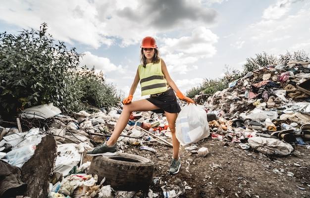 Женщина-волонтер помогает очистить поле от пластикового мусора и старых шин. день земли и экология. Premium Фотографии