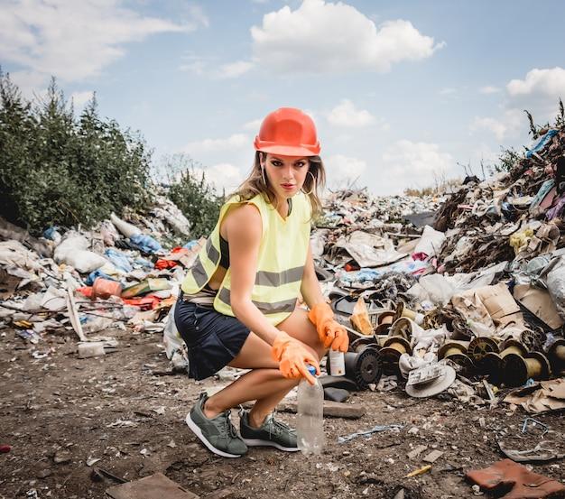 Женщина-волонтер помогает очистить поле от пластикового мусора. день земли и экология. Premium Фотографии