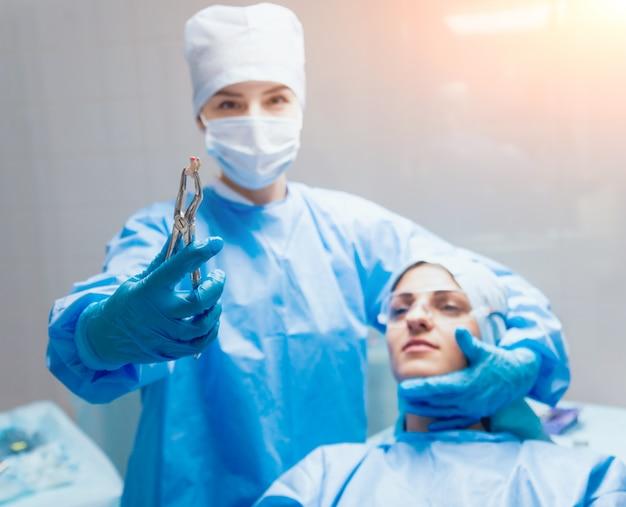 Стоматолог с помощью хирургических плоскогубцев, чтобы удалить гниющий зуб. современная стоматологическая клиника Premium Фотографии
