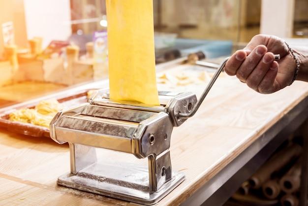 Шеф-повар раскатывает тесто с помощью машины для макарон Premium Фотографии