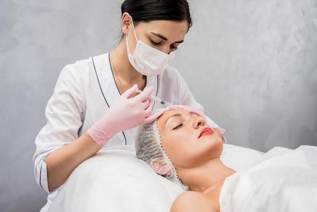 Врач косметолог проводит процедуру инъекций лица. молодая женщина в салоне красоты. Premium Фотографии
