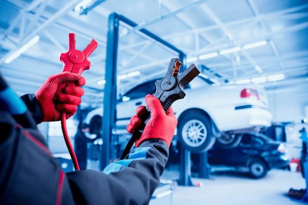 Зарядка аккумулятора. руки и терминалы. ремонт машин. Premium Фотографии