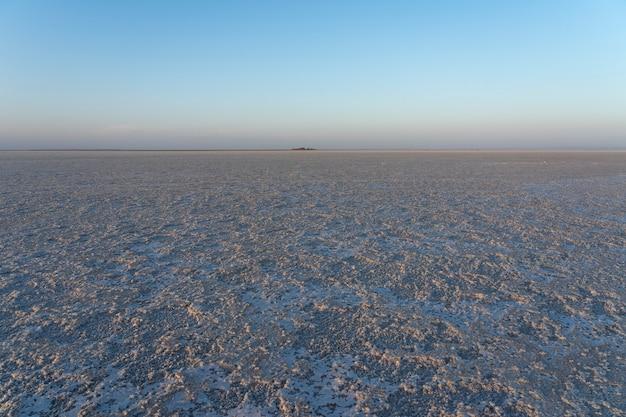 アフリカ、エチオピアのダナキル恐慌のアセール湖の塩原に沈む夕日 Premium写真