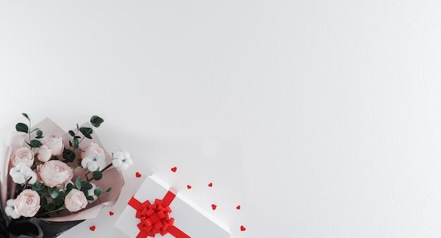 赤いリボンと白い背景の上のハート型の紙吹雪と白いギフトボックスに花の美しい花束。バレンタイン・デー Premium写真