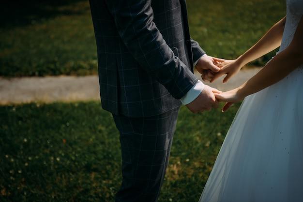 緑の草の背景に手を繋いでいる結婚式のテーマ。新郎新婦のクローズアップの手。結婚式の日のカップル、感動的な瞬間。 Premium写真
