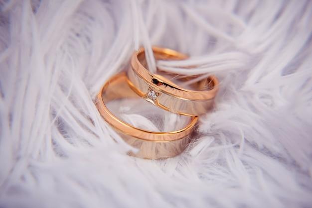 Изображение содержит золотое кольцо с бриллиантом, лежащее на белых перьях. обручальные кольца, брак, помолвка, роскошь, украшения и т. д. Premium Фотографии