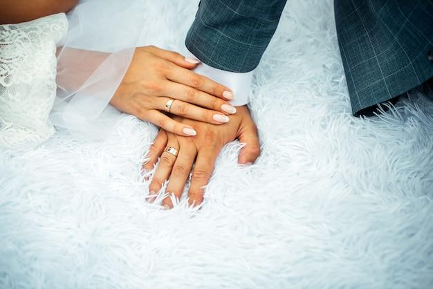 Жених и невеста держа руки с рукой женщины на руке человека с обручальными кольцами, конец вверх. руки молодоженов в день свадьбы. стильное фото. Premium Фотографии
