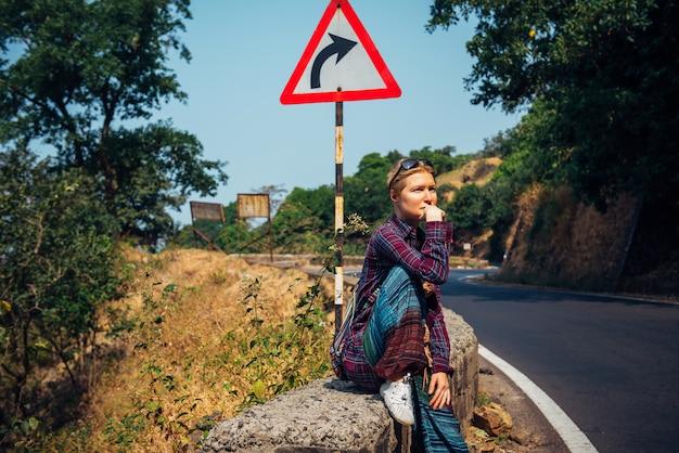 Турист детенышей довольно женский на обочине дороги ждать проходя автомобиль на солнечный день. стильная блондинка автостопом в азии. свобода, независимость, приключение Premium Фотографии