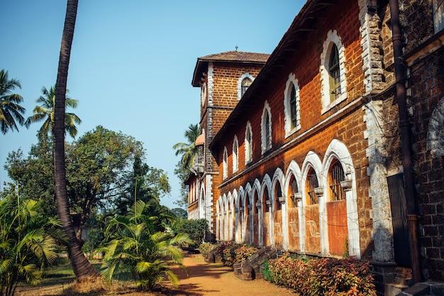 窓と塔のある古い赤レンガの建物の断片。歴史的建造物、植民地時代のインドの建築 Premium写真