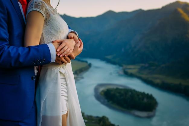 山と川の絶景を望む新婚夫婦の手をつなぐ結婚式のテーマ Premium写真