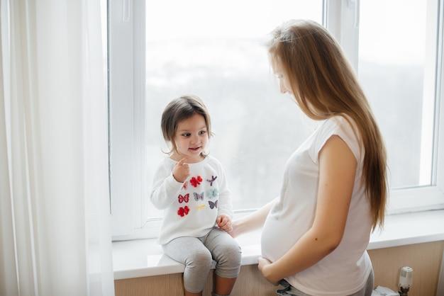 Беременная мать стоит возле окна со своей маленькой дочерью Premium Фотографии
