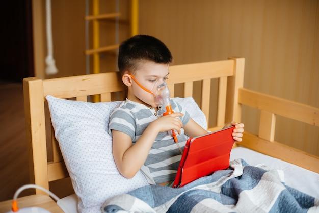 Мальчик играет на планшете во время процедуры ингаляции легких. медицина и уход Premium Фотографии