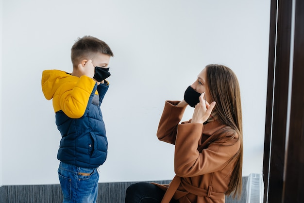 Мать с ребенком стоит в маске во время карантина Premium Фотографии