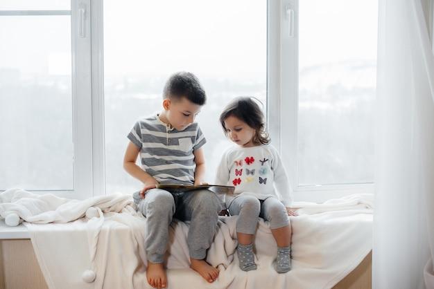 兄と妹は窓辺に座って本を読んでいます。幸せ、家族 Premium写真