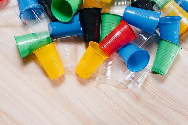 色とりどりのプラスチック製のコップの大きな山が空きスペースのある床に散らばっています。し尿による環境汚染 Premium写真