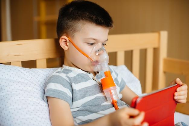 Мальчик играет на планшете во время процедуры ингаляции легких. Premium Фотографии
