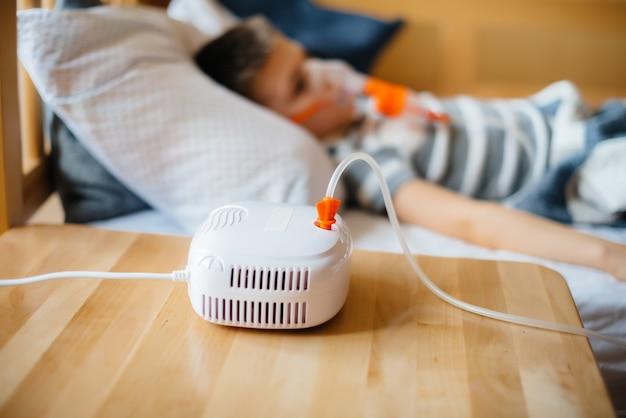 Молодому мальчику делают ингаляцию при заболевании легких. медицина и уход. Premium Фотографии