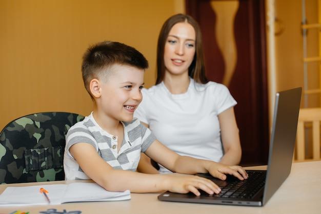 Мать и ее ребенок занимаются дистанционным обучением дома перед компьютером. сиди дома, тренируйся. Premium Фотографии