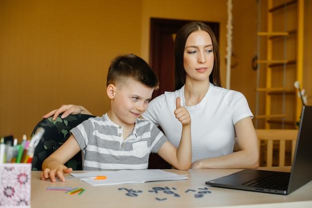 Мать и ее ребенок занимаются дистанционным обучением дома перед компьютером. Premium Фотографии