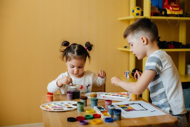 男の子と女の子が一緒に遊び、ペイントします。レクリエーションとエンターテイメント。家にいる。 Premium写真