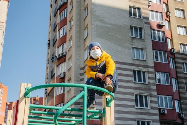 Маленький мальчик в маске гуляет по детской площадке во время карантина. останься дома. Premium Фотографии