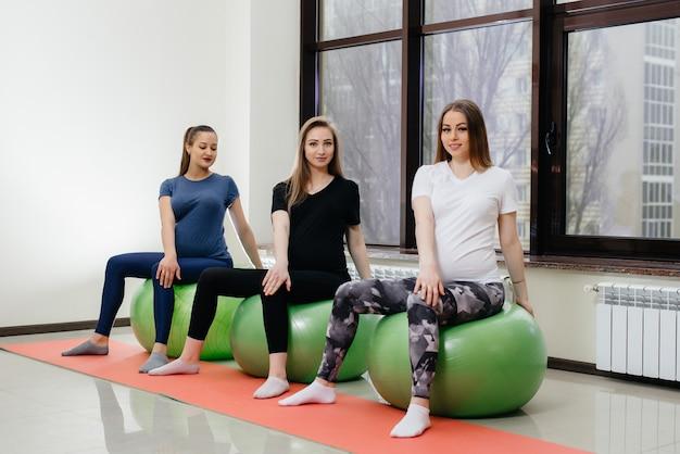 Группа молодых беременных мам занимается пилатесом и мячом в фитнес-клубе. беременная Premium Фотографии