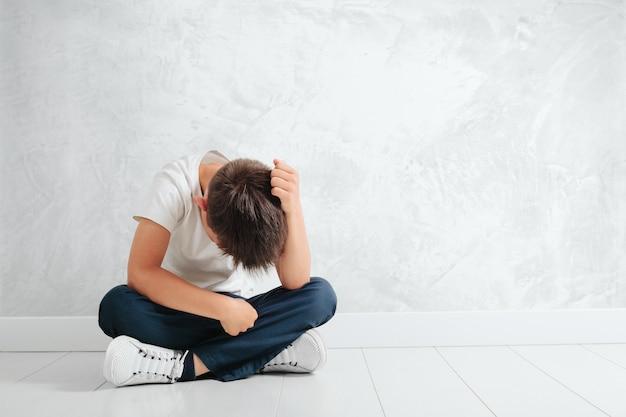 Ребенок, чья депрессия сидит на полу Premium Фотографии
