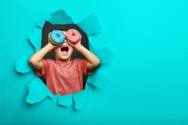 幸せなかわいい男の子は黒い背景の壁にドーナツで遊んで楽しんでいます。子供の明るい写真。 Premium写真
