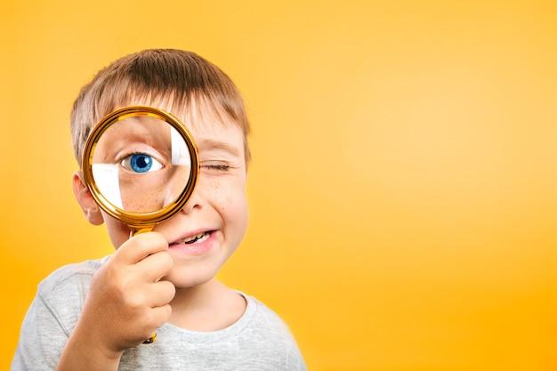 Ребенок видит сквозь увеличительное стекло на цветном желтом фоне. Premium Фотографии