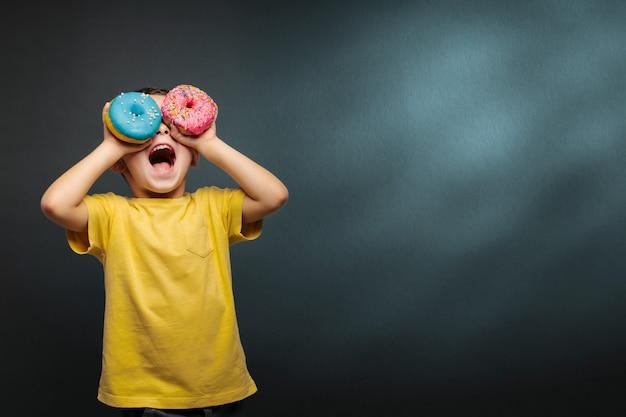 Счастливый милый мальчик весело играет с пончики на черном фоне стены. Premium Фотографии