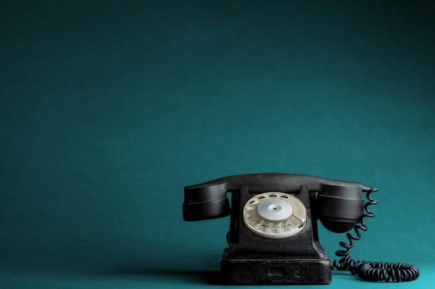 Старый телефон на бирюзовом фоне Premium Фотографии
