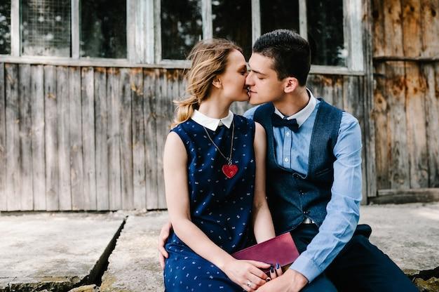 座って、キスしてハグする若いカップルが、窓のある木造の古い家の近くに閉じた本を手に持っています。閉じる。 Premium写真